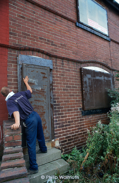 Sealing up an empty house in the former pit village of Grimethorpe, South Yorkshire, which has undergone serious decline since its colliery closed in 1993.