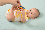 4 month old baby girl on back full length reaching up to touch dangled toy with colorful wooden rings