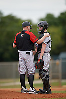 Edgewood Eagles head coach Al Brisack talks with catcher Alex Prindle (15) and starting pitcher Will Mossa (hidden) during the first game of a double header against the Bethel Wildcats on March 15, 2019 at Terry Park in Fort Myers, Florida.  Bethel defeated Edgewood 6-0.  (Mike Janes/Four Seam Images)