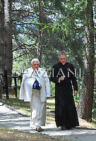 Pope Benedict XVI is seen wearing a cast on his right arm as he goes for a walk in Les Combes, near Aosta, northern Italy, Saturday, July 18, 2009. Benedict XVI spent an easy night after breaking his wrist in his Alpine vacation chalet and is learning to cope with the cast on his right arm, the Vatican said Saturday. .