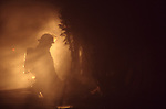 A fire fighter kneeling next to a house that was damaged by fire and smoke with light beams through the smoke