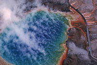 Aerial of boiling water of Grand Prismatic, a geothermic pool in Yellowstone National Park. More than 90 percent of the world's geothermal activity resides in the boundaries of the park.  Steam rises from the largest hot spring in the United States. and measures 250 by 300 feet and 160 feet deep.<br /> The vivid colors in the spring are the result of pigmented bacteria in the microbial mats that grow around the edges of the mineral-rich water. <br /> The bacteria produce colors ranging from green to red; the amount of color in the microbial mats depends on the ratio of chlorophyll to carotenoids. In the summer, the mats tend to be orange and red, whereas in the winter the mats are usually dark green.<br /> The center of the pool is sterile due to extreme heat.<br /> The deep blue color of the water in the center of the pool results from a light-absorbing overtone of the hydroxy stretch of water.Though this effect is responsible for making all large bodies of water blue, it is particularly intense in Grand Prismatic Spring because of the high purity and depth of the water in the middle of the spring.
