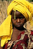 The Gambia; girl in a yellow turban headdress and torn print dress.