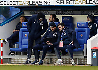 13th February 2021; Madejski Stadium, Reading, Berkshire, England; English Football League Championship Football, Reading versus Millwall; Millwall Manager Gary Rowett with his coaching staff looking at a computer tablet in the dugout