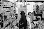 Arabs London UK 1977. Middle Eastern people came to Britain for subsidised health care carried out in Harley Street clinics. They mainly stayed in the Earls Court area. Arab woman shopping in chemist shop.