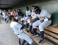 Infielder Angelo Gumbs (21) of the Charleston RiverDogs, left, encourages teammate infielder Reymond Nunez (25) in the dugout just before a game against the Greenville Drive on May 31, 2012, at Fluor Field at the West End in Greenville, South Carolina. Charleston won, 13-2.  (Tom Priddy/Four Seam Images)