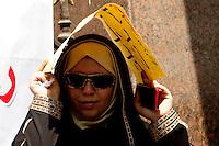 EGITTO, IL CAIRO 9/10 settembre 2011: assalto all'ambasciata israeliana. Migliaia di manifestanti egiziani, ancora infuriati per l'uccisione di cinque guardie di frontiera egiziane da parte dell'esercito israeliano, hanno fatto irruzione nella sede diplomatica israeliana e sono stati poi sgomberati da esercito e polizia egiziana. Nell'immagine: una donna con velo e occhiali da sole si protegge dal sole con un foglio di carta. In mano ha un cellulare.