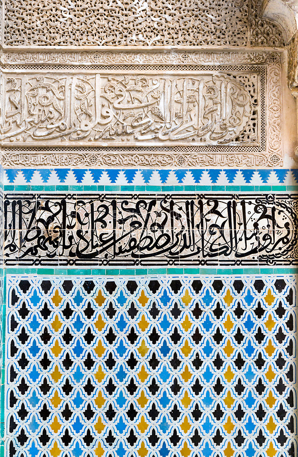 Fes, Morocco.  Attarine Medersa, 14th. Century.  Decorative Tile Work under Arabic Calligraphy on Tiles, under Calligraphy on Stucco.