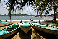 Fishing boats sit on the shores of  Zihuatanejo's Playa Madera beach. Zihuatanejo, the twin sister town of Ixtapa, continues its history as a fishing village while nearby Ixtapa has been transformed into a master-planned resort with high-rise hotels and trendy restaurants.  (taken August 2007). Photo by Patrick Schneider Photo.com