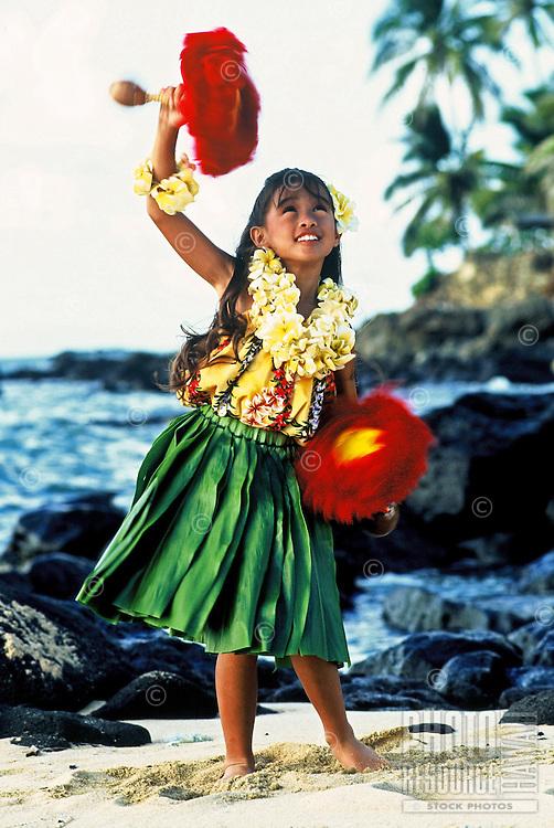 Beautiful young Hawaiian girl (age 7)with uli uli (rattles), plumeria leis and ti leaf skirt performing a hula