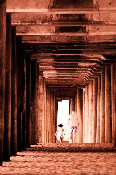 Man and girl walking under the pier.  Taken with infrared.