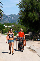 A young woman in jeans hotpants shorts with naked belly and black tanktop tank top and an old woman with a walking stick and a long skirt with flowery pattern walking along a foot path by the beach Orebic town, holiday resort on the south coast of the Peljesac peninsula. Orebic town. Peljesac peninsula. Dalmatian Coast, Croatia, Europe.