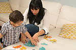 Two year old toddler boy doing cardboard jigsaw puzzle with mother's help, talking, mother steadying pieces to assist him