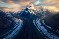 Glaciers converge at the foot of Mt. Hess as the rising sun filters through the clouds.