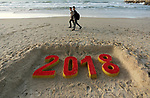 Palestinians man walk past a 2018 sand writing at a beach in Gaza City on December 31, 2017 on the last day of the year. Photo by Ashraf Amra