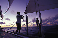 Man trimming sails after sunset aboard sailing yacht 'Heron', a Halberg-Rassy 46, in tropical waters
