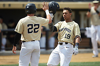 Christian Long (19) of the Wake Forest Demon Deacons is greeted at home plate by teammate Michael Ludowig (22) after hitting a home run against the Virginia Cavaliers at David F. Couch Ballpark on May 19, 2018 in  Winston-Salem, North Carolina.  The Demon Deacons defeated the Cavaliers 18-12.  (Brian Westerholt/Four Seam Images)