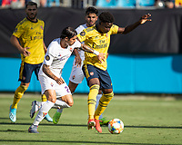 CHARLOTTE, NC - JULY 20: Bukayo Saka #77 and Lorenzo Venuti #2 go for the ball during a game between ACF Fiorentina and Arsenal at Bank of America Stadium on July 20, 2019 in Charlotte, North Carolina.