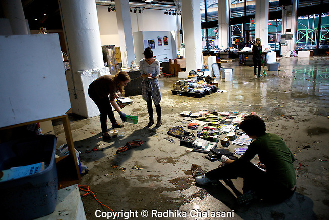 BROOKLYN, NEW YORK-OCTOBER 30: People clean up Powerhouse Books after the DUMBO, Brooklyn waterfront flooded during the night from Hurricane Sandy October 30, 2012. U.S. President Barack Obama declared large areas of the East Coast a major disaster area. © Radhika Chalasani