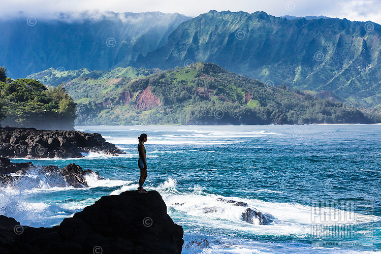 A woman contemplates Hanalei Bay while waves break around her, Kaua'i.