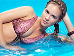 Beauty portrait of a young woman with braided long hair wearing a swimsuit lying in blue water Image © MaximImages, License at https://www.maximimages.com