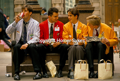 LIFFE, London International Financial Futures Exchange. Young traders known as Yellow Jackets, having a lunch break. This  was all pre-computer trading, and is where deals were struck, Derivates, Options and Futures were bought and sold by shouting across the trading floor know at the 'Bear Pit' and frantic gesturing. They wore different coloured jackets so that colleagues could pick each other out in the frenzy of a days work.