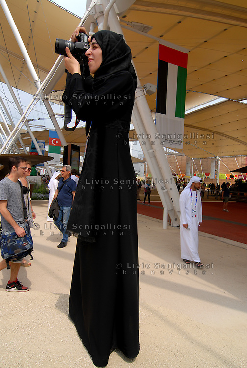 Milano - Rho Fiera 1/6/2015<br /> EXPO 2015, una donna nel tradizionale abito arabo, membro dello staff del padiglione degli Emirati Arabi Uniti, fotografa i visitatori.<br /> Woman in traditional Arab dress, staff member of the United Arab Emirates, photographing visitors outsite the pavillon. <br /> Foto Livio Senigalliesi