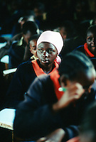 Kenya. Rift Valley Province. Mwenja. Primary school.  Classroom. A student listens to his teacher's lesson. The girl is wearing a green and orange uniform. © 2004 Didier Ruef
