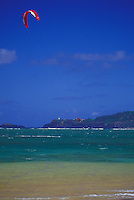 Kite surfer jumping in clear lagoon waters off Anini Beach, east side of Kauai