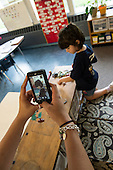 MR / Schenectady, NY. Zoller Elementary School (urban public school). Kindergarten classroom. Teacher uses smartphone camera to photograph student (girl, 5) at play. Photographs in this classroom are used as an assessment tool for student's cognitive, emotional, and social growth throughout the schoolyear. MR: Coh2. ID: AM-gKw. © Ellen B. Senisi.