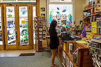 A customer makes a purchase at Basic Books, a bookstore with used and new books, downtown Hilo, on the Big Island of Hawai'i.