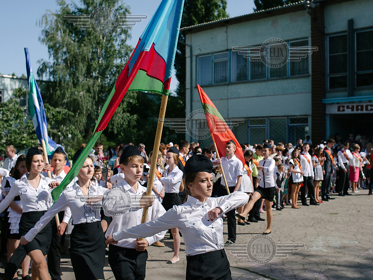 Students of the school N9 carry the state and regional flags during the Last Bell ceremony, at the end of the school year.