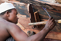 Nungwi, Zanzibar, Tanzania.  Dhow Construction.  Marking a line for cutting to smooth the joint between two planks of the hull.