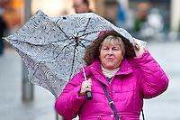 Friday 31 January 2014<br /> Pictured: A woman walks through Carmarthen town centre clutching a broken umbrella<br /> Re: Severe weather warnings are issued accross Wales and England