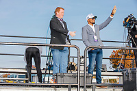 Mike Nificent (right) and Alex Caldwell, commentators on the rightwing Right Side Broadcasting Network, wave to the crowd from the press riser before the arrival of US President Donald Trump at a Make America Great Again Victory Rally in the final week before the Nov. 3 election at Pro Star Aviation in Londonderry, New Hampshire, on Sun., Oct. 25, 2020. Right Side Broadcasting Network is an online network devoted to showing full-length Trump campaign rallies.