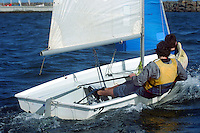 A sailor guides his small sailboat through the water.