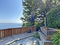 BNPS.co.uk (01202) 558833. <br /> Pic: LillicrapChilcott/BNPS<br /> <br /> Pictured: Garden with wood-fired hot tub. <br /> <br /> A pretty wooden cottage with spectacular panoramic sea views is on the market for £595,000.<br /> <br /> The aptly-named The Hut is an eco-built property set on a hill in the hugely sought-after Cornish village of Mousehole.<br /> <br /> The small but perfectly-formed home looks down over Mousehole harbour and across Mounts Bay to St Michael's Mount.