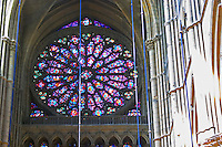 The Reims Cathedral: the stained glass of the famous rosette, Reims, Champagne, Marne, Ardennes, France, low light grainy grain