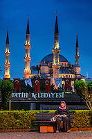 Fine Art Print Photography. World cultures. A night scene photograph of a Turkish woman sitting on a park bench in front of a Mosque in Istanbul, Turkey.<br /> The blue night sky mixed with the warm tungsten lighting bring out the details of the domes and the minarets of the Mosque.<br /> The Muslin lady's presence on the park bench<br /> completes the story of this scene.