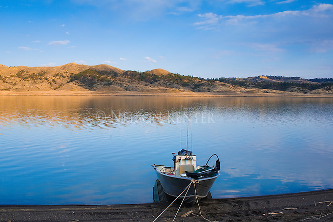A fishing boat is tied to the shore of the Missouri River on a summer evening in Montana