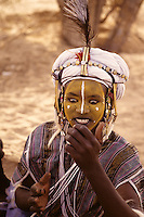 Akadaney, Niger, Africa - Fulani Wodaabe Dancer at Geerewol, checks his appearance in a mirror before participating in what westerners often call the male beauty contest, in which the whiteness of the eyes and the teeth is an important factor in appealing to the female spectators.