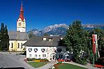 Austria, Tyrol, Igls near Innsbruck: parish church and tourist-office at village centre and Nordkette mountain