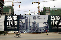 A man cycles past a huge billboard featuring the on building China Central Place near Chang An Street in Beijing China..29-MAY-04