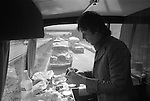 """Paul and Linda McCartney Wings Tour 1975. Paul making a sandwich at the back of the tour bus. He has two Rolls Royce cars following behind the coach, for his use should he need them. The photographs from this set were taken in 1975. I was on tour with them for a children's """"Fact Book"""". This book was called, The Facts about a Pop Group Featuring Wings. Introduced by Paul McCartney, published by G.Whizzard. They had recently recorded albums, Wildlife, Red Rose Speedway, Band on the Run and Venus and Mars. I believe it was the English leg of Wings Over the World tour. But as I recall they were promoting,  Band on the Run and Venus and Mars in particular."""