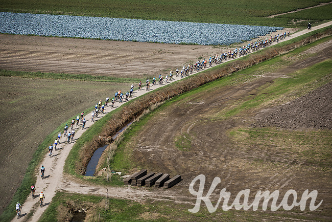 """Peloton riding the  gravel roads. <br /> <br /> Antwerp Port Epic 2018 (formerly """"Schaal Sels"""")<br /> One Day Race: Antwerp > Antwerp (207km of which 32km are cobbles & 30km is gravel/off-road!)"""