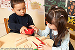 Education preschool 3-4 year olds boy and girl playing together with blocks boy handing girl block sharing horizontal