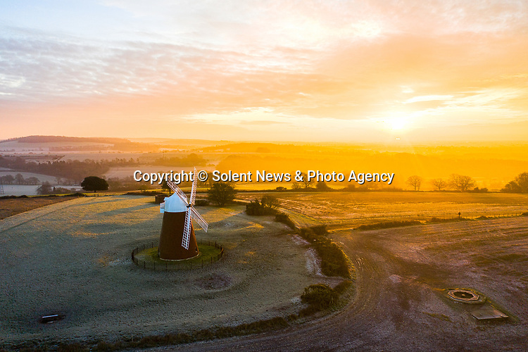 UK WEATHER INPUT<br /> <br /> Pictured: A man walks along the path leading down from Halnaker Windmill against a golden sunrise this morning in Halnaker, West Sussex.<br /> <br /> With parts of the country experiencing snow fall overnight, it was an unseasonably bright and sunny start down in the south with temperatures hitting a maximum of 3 degrees celcius. <br /> <br /> © Jordan Pettitt/Solent News & Photo Agency<br /> UK +44 (0) 2380 458800