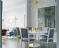 Chevron fabric adds a modern kick to these classic dining chairs as they encircle an equally-classic Eero Saarinen Tulip Table.A further modern twist is introduced with a gold starburst chandelier adding some drama to the space. A soft rug marks the point where you enter the living area.
