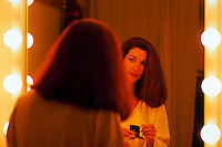 Woman looking at herself in a mirror and applying makeup.