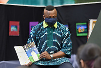"""Artist Ibi Olufemi Alao reads to Elmwood Middle School students from his book """"Ibi's Fireflies"""", Friday, April 30, 2021 at the Rogers Experimental House in Rogers. About 30 eighth-grade art students from Elmwood Middle School went on an art tour through downtown Rogers at the Anime Cafe, White's Jewelry and the Rogers Experimental House where they met resident artist Ibi Olufemi Alao. Check out nwaonline.com/210501Daily/ for today's photo gallery. <br /> (NWA Democrat-Gazette/Charlie Kaijo)"""